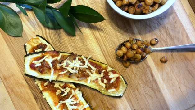 Zucchini stuffed with tomato sauce, fried onions and topped with vegan cheese